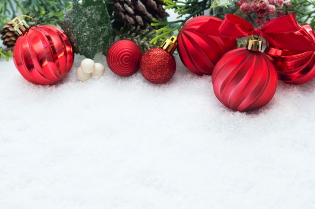 Red christmas baubles with fir branches, pine cones, on white snow background. winter holidays.