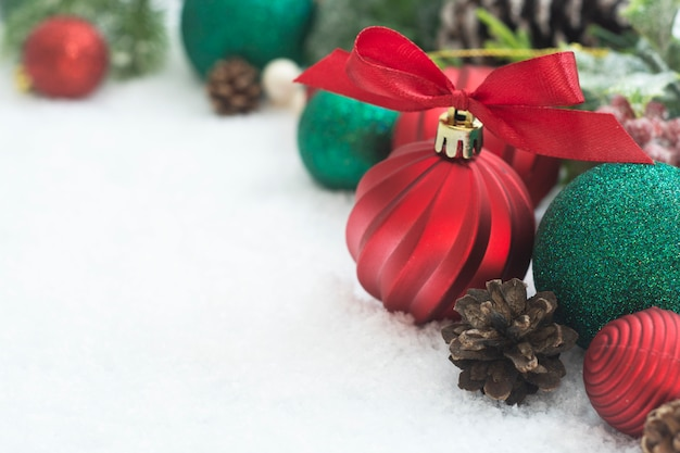 Red christmas baubles with fir branches, pine cones, on white snow.