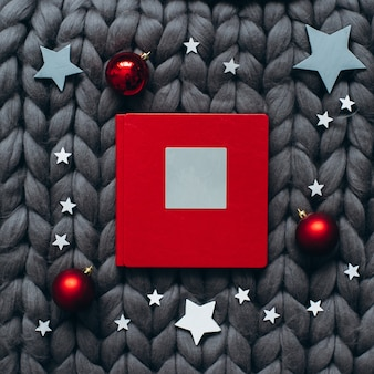 Red christmas book with balls in the grey knitted blanket