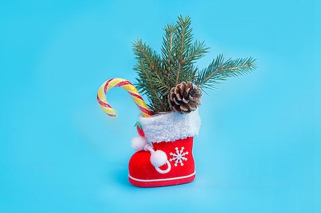 Красный рождественский сапог с еловыми ветками, еловой шишкой и леденцом на синем фоне