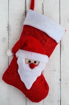 白い背景の上のサンタクロースのテキスタイルヘッドと赤いクリスマスブーツ。