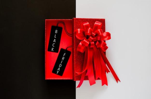 Красная рождественская коробка с красной лентой-бантом и черным ценником на черно-белом