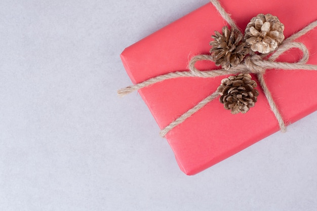 Красная новогодняя коробка с тремя шишками на белой поверхности