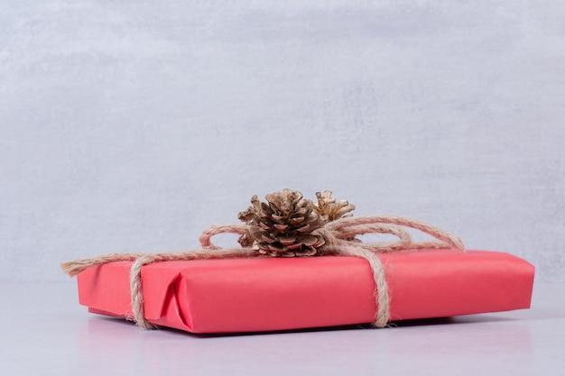 白いテーブルの上に3つの松ぼっくりが付いている赤いクリスマスボックス。