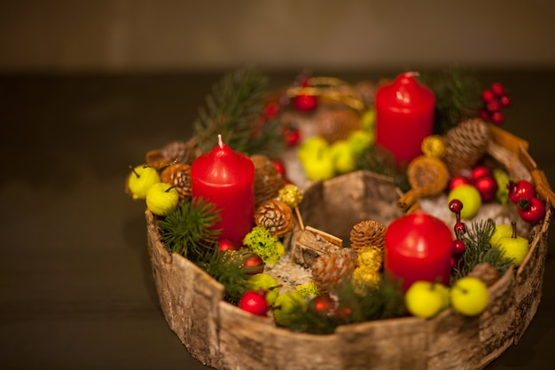 Red christmas candle in a basket with berries and fir cones with green apples