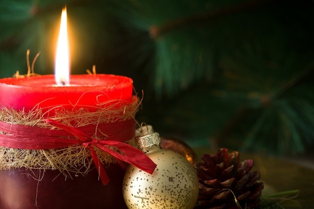 Red christmas candle and christmas ornaments on wood copy space