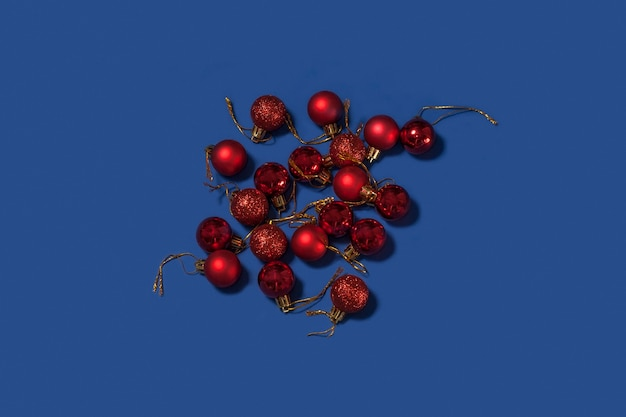 青い背景の上の赤いクリスマスの装飾ボール。メリークリスマスカード。