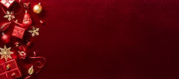 Красные рождественские украшения безделушка и лента на фоне стола из бархатной красной фетровой ткани