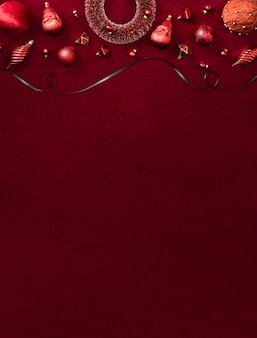Red christmas decoration bauble and ribbon on velvet red felt fabric  top view table backgorund