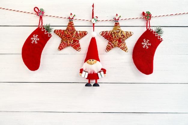 Красное украшение рождества на белой деревянной предпосылке. copyspace. санта фон.