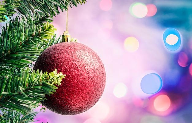 焦点がぼけた色のライトを背景に木の枝に赤いクリスマスの装飾