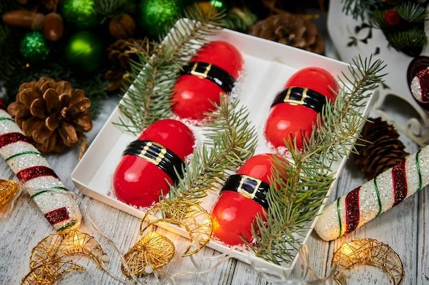 キャンドルの花輪モミの枝の背景にムースの形で赤いクリスマスデザート