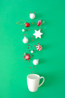 Red christmas elements fall into a white cup on a green surface