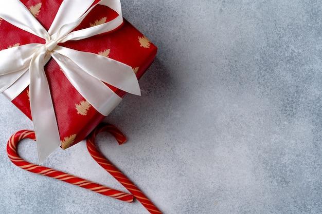 Красная рождественская подарочная коробка на сером матовом фоне, вид сверху