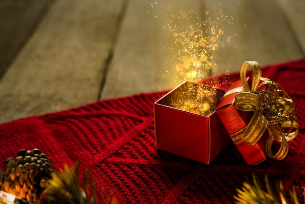 Red christmas gift box on red scraf with gold particles light magical on wooden desk.