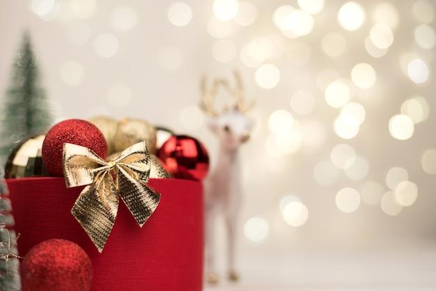 Красная рождественская подарочная коробка с золотым бантом на фоне боке, елок и игрушек.
