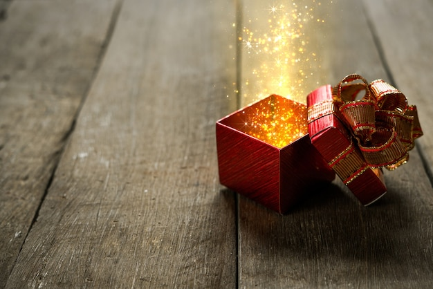 Red christmas gift box with gold magic lights on wooden desk.