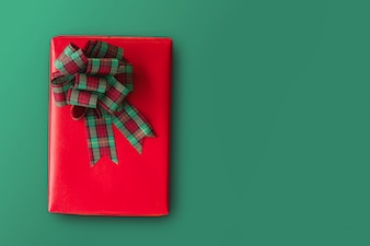 Red Christmas gift box with green ribbon bow on green background with copy space