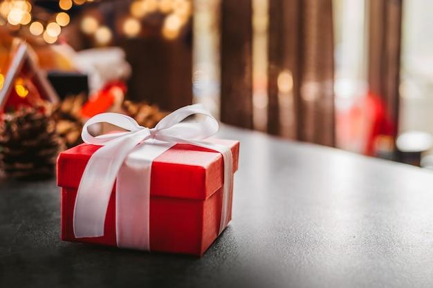 Красная рождественская подарочная коробка с белой лентой o