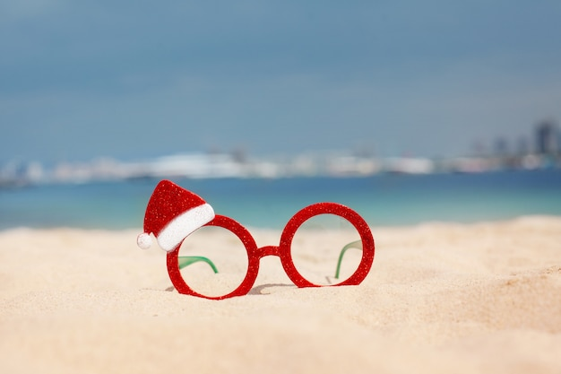 Red christmas glasses and santa hat on the beach