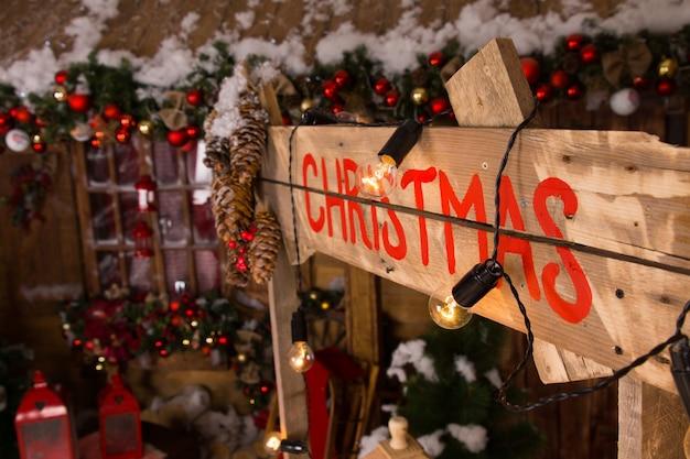 家の中のライトとクリスマスの飾りが付いている木製のブースの壁の赤いクリスマスのラベル。