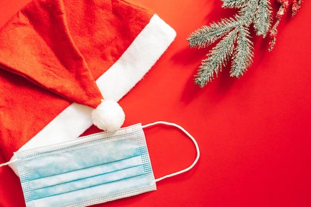 Красная шляпа санта-клауса рождества с маской. красный фон украшения. рождество с covid.