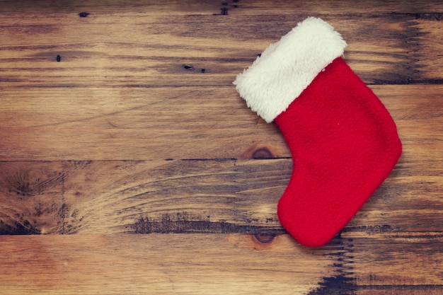 Red christmas sock hanging on brown wooden background