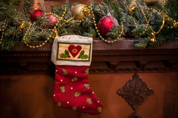 Red christmas sock hanging on the fireplace. spruce branches, toys christmas mood