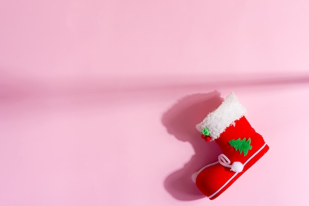 Красный новогодний носок с праздничным декором на пастельно-розовом. вид сверху.
