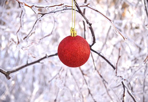 氷で覆われた木の凍った枝にぶら下がっている赤いクリスマスのおもちゃ