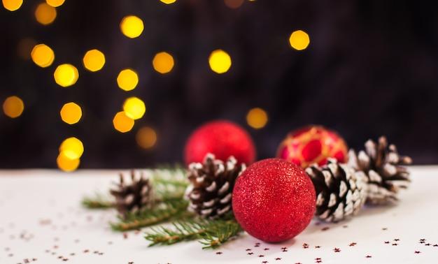 Красные елочные игрушки и сосновые шишки лежат на белом фоне с боке