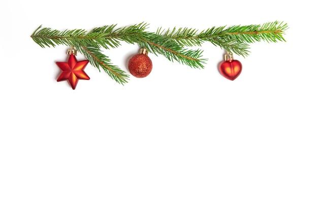 赤いクリスマスのおもちゃと白い孤立した背景にトウヒの小枝。デザイン要素。
