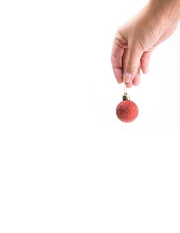 手に赤いクリスマスツリーボール