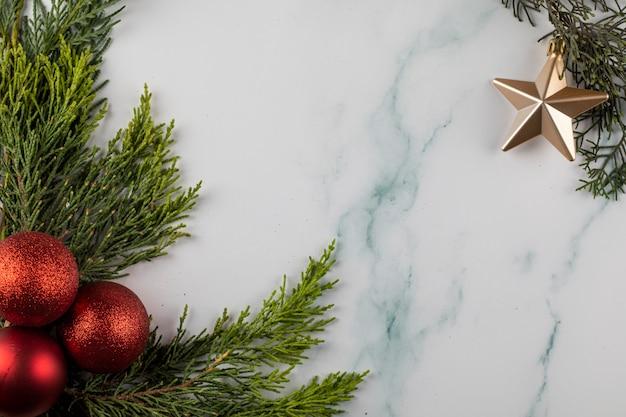 緑の枝と反対側の隅にある金色の星に赤いクリスマスツリーのボール。