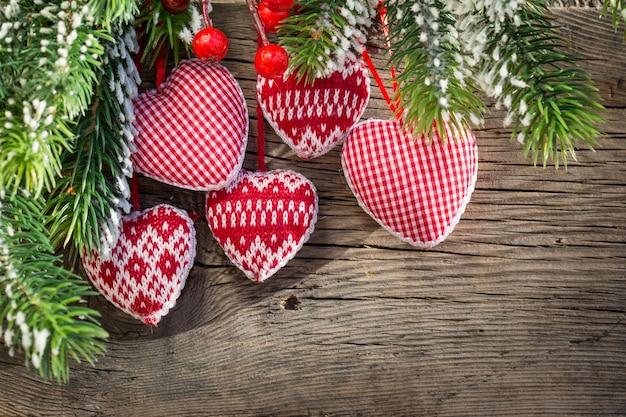 赤いクリスマスツリーの装飾は、木の背景に緑の枝を額装