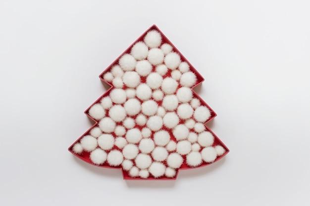 白い表面に白いふわふわのつまらないボールで満たされた赤いクリスマスツリーのシルエットのアウトライン。