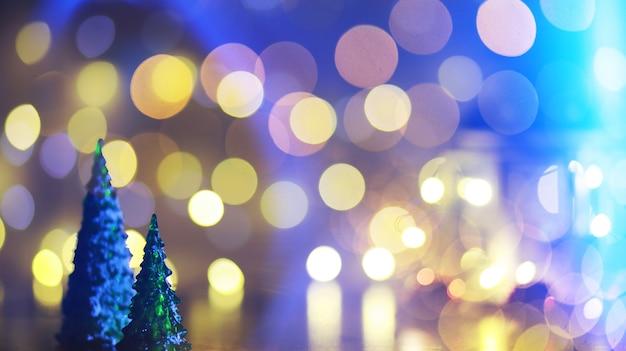 背景に焦点がぼけた花輪のライトが付いている自然なモミの木の枝に赤いクリスマスツリーのおもちゃ。鹿と雪片のスリットが入った金属製のおもちゃ。クリスマス、新年、コピースペース、ボケ味。