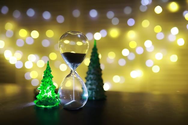 Красная елочная игрушка на ветке натуральной ели с огнями гирлянд в расфокусировке на заднем плане. металлическая игрушка с прорезями оленей и снежинок. рождество, новый год, копия пространства, боке.