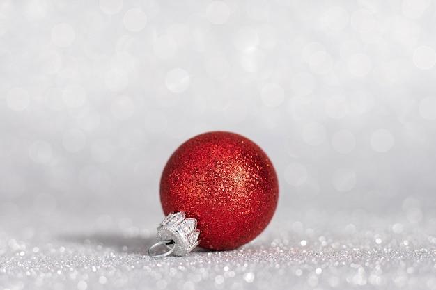 白い背景の上の赤いクリスマスツリーのおもちゃ。白い表面のクリスマスの装飾。