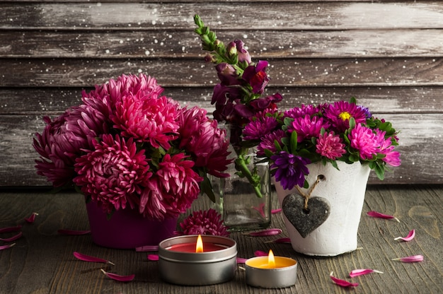 Красные цветы хризантемы и зажженные свечи