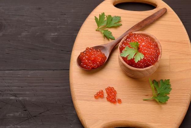 Красная икра кеты в деревянной миске, вкусная и здоровая еда, вид сверху