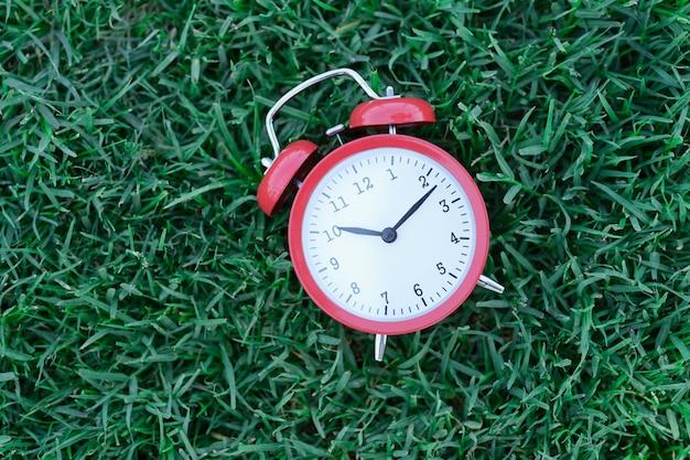 푸른 잔디 근접 촬영에 누워 레드 클래식 알람 시계
