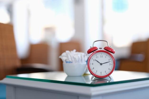 카페 근접 촬영에서 테이블에 서 있는 빨간색 클래식 알람 시계