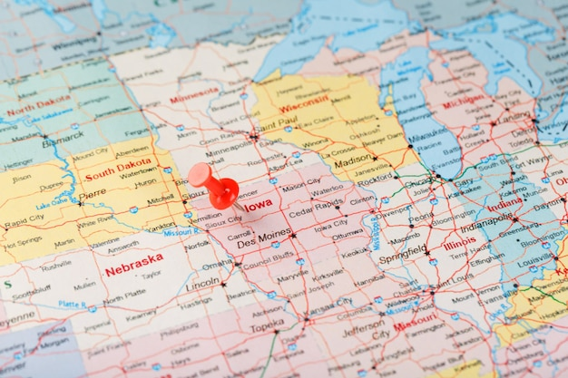 Red clerical needle on a map of usa, iowa and the capital des moines. close up map of iowa with red tack