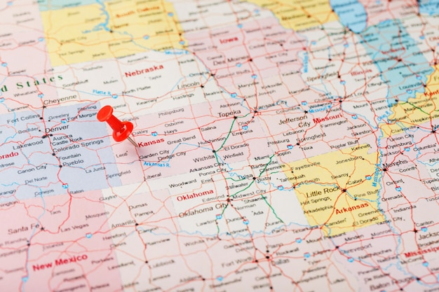 Red clerical needle on a map of usa, kansas and the capital topeka. close up map of kansas with red tack