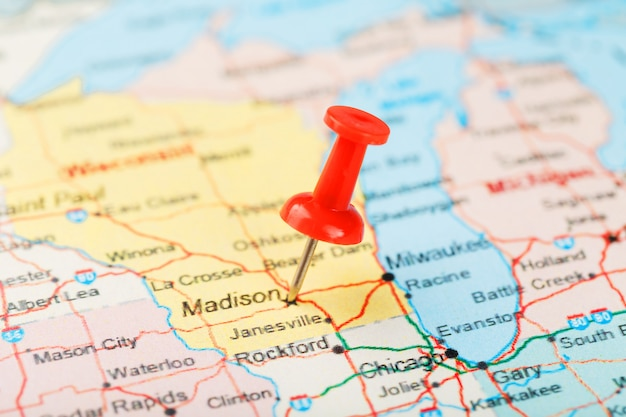 Red clerical needle on a map of usa, michigan and the capital lansing. close up map of michigan with red tack