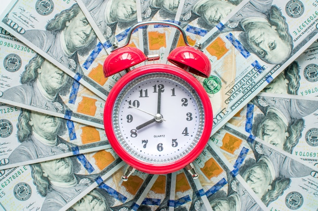 Red clock on the background of money dollars