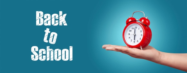 Red clock with alarm on hand over blue background, panoramic image with inscription back to school