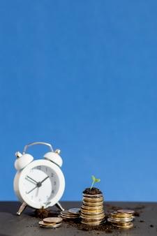 コインと赤い時計お金と金融のビジネスコンセプトを節約します。ビジネスファイナンスと将来の準備のためのお金を節約。時間はお金の概念です。