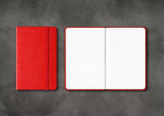 어두운 콘크리트 표면에 고립 된 빨간색 닫힌 및 열린 줄 지어 노트북 모형